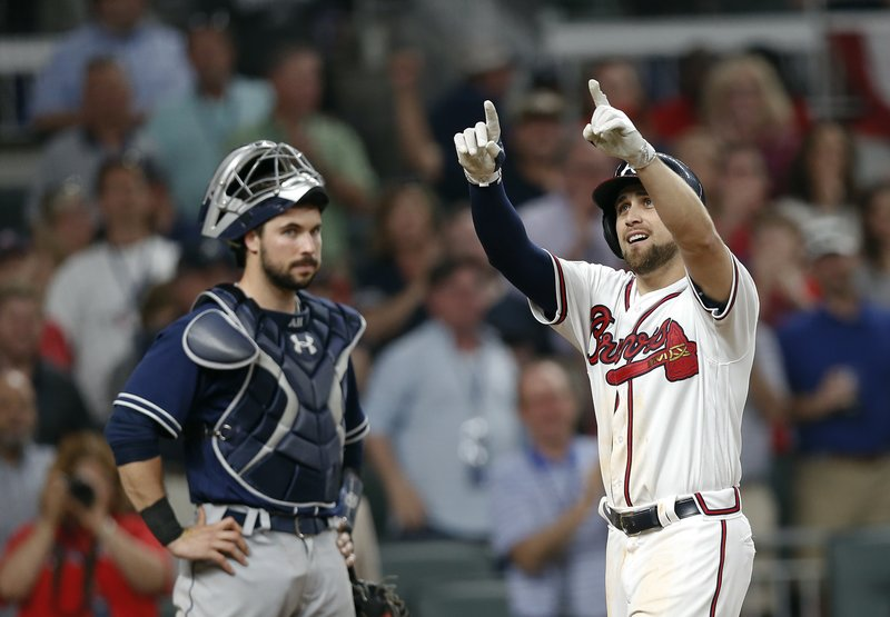 Atlanta Braves' Ender Inciarte, right, gestures as he crosses home plate in front of San Diego Padres catcher Austin Hedges, left, after hitting a two-run home run in the sixth inning of a baseball game Friday, April 14, 2017, in Atlanta. The home run was the first hit in Sun Trust Park. (AP Photo/John Bazemore)