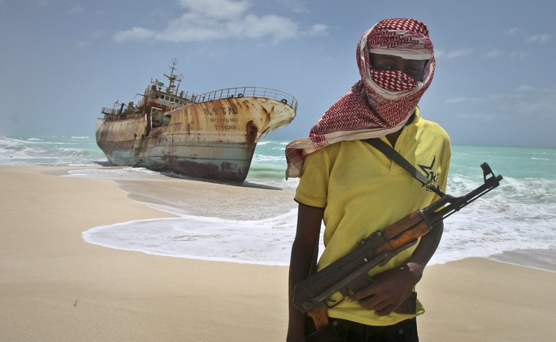 In this Sunday, Sept. 23, 2012 file photo, masked Somali pirate Hassan stands near a Taiwanese fishing vessel that washed up on shore after the pirates were paid a ransom and released the crew, in the once-bustling pirate den of Hobyo, Somalia. Somali pirates have seized a small boat, kidnapped its Indian crew members, and are taking the vessel to the Eyl area of northern Somalia, an investigator said Monday, April 3, 2017, the latest vessel targeted by the region's resurgent hijackers.