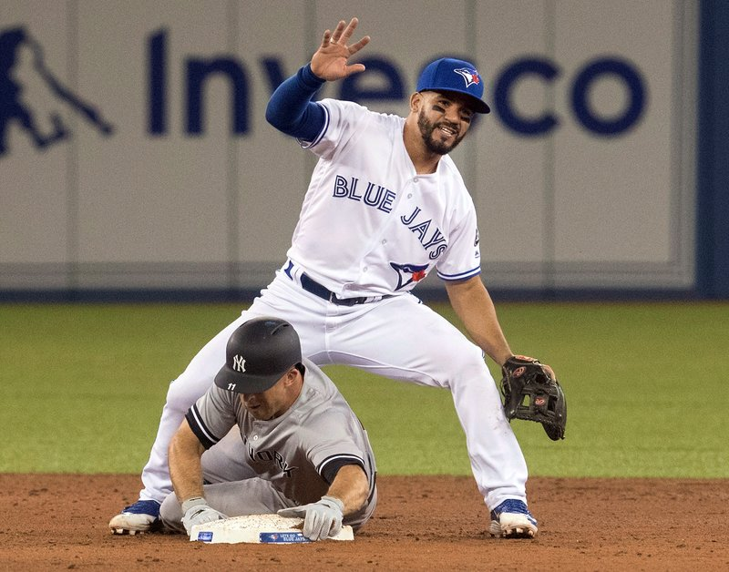 New York Yankees Brett Gardner is out on the force out at second base sliding through the legs of Toronto Blue Jays Devon Travis