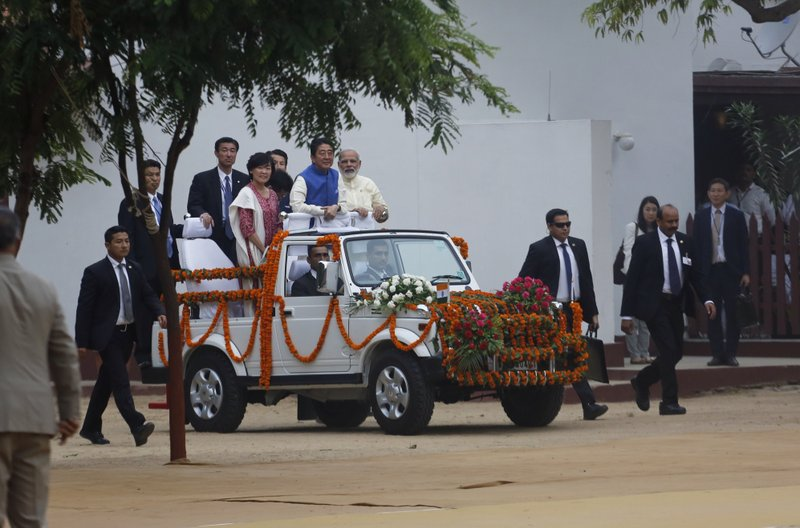 Japanese Prime Minister Shinzo Abe, center, accompanied by his wife Akie Abe, and Indian Prime Minister Narendra Modi arrive on an open vehicle at Sabarmati Ashram, or Gandhi Ashram, in Ahmadabad, India, Wednesday, Sept. 13, 2017. Abe is on a two-day official visit to India.