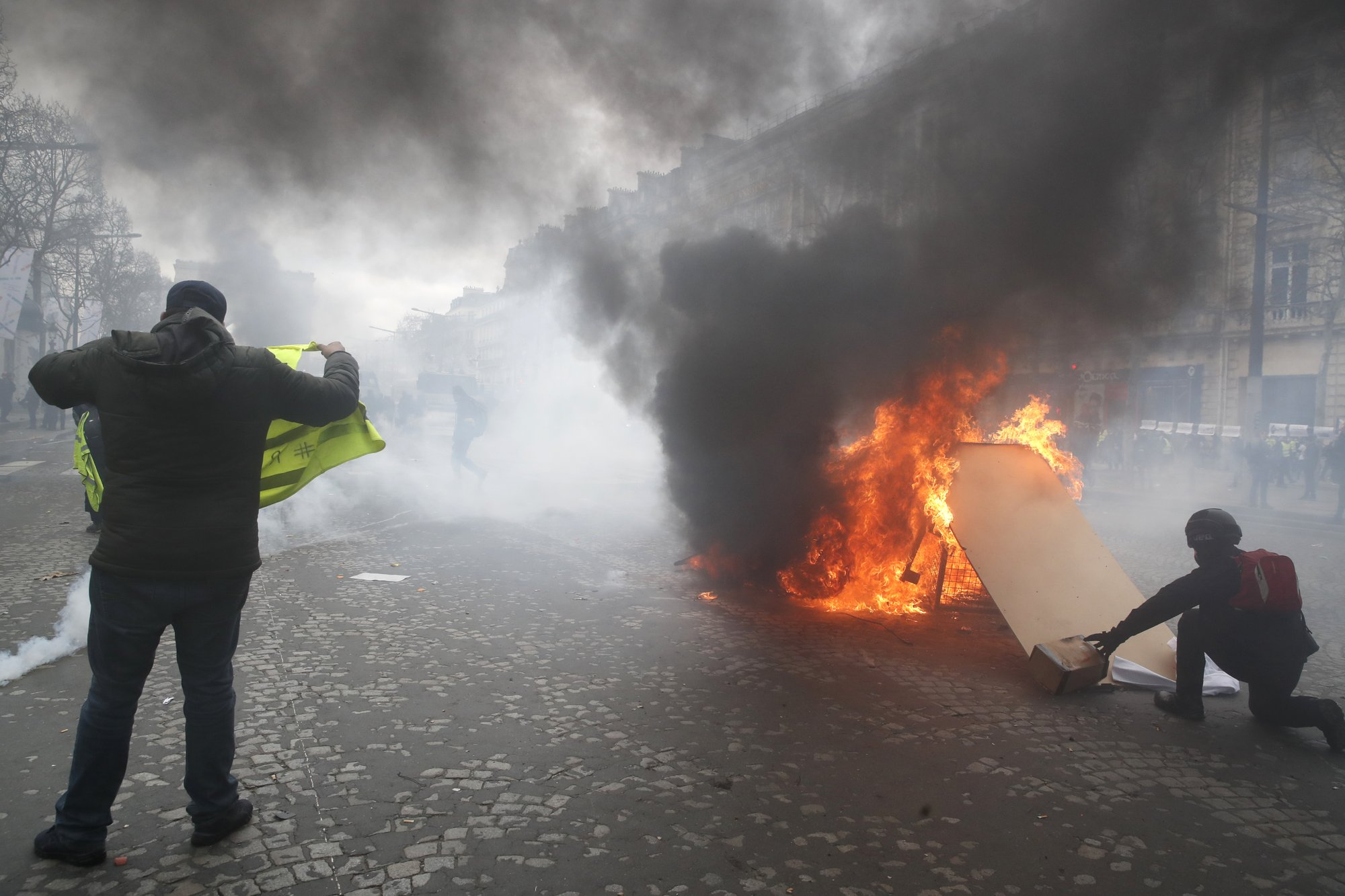 """French protesters riot in Paris, accuse Macron of """"hot air"""""""