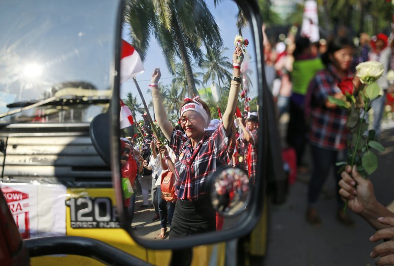 "A supporter of Jakarta Governor Basuki ""Ahok"" Tjahaja Purnama dances as her reflection is seen on the mirror of a truck parked outside the court where his sentencing hearing is held in Jakarta, Indonesia, Tuesday, May 9, 2017. The minority Christian governor is currently on trial on accusation of blasphemy following his remark about a passage in the Quran that could be interpreted as prohibiting Muslims from accepting non-Muslims as leaders."