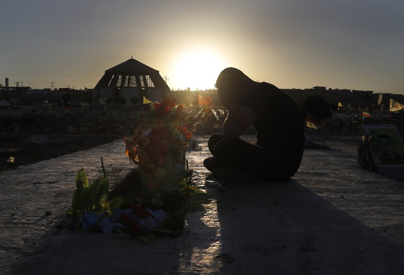 A Kurdish man mourns as he sits next to the grave of his friend who was killed while fighting against Islamic State militants in Raqqa, at a cemetery in Kobani, Syria, Friday, July 28, 2017. Islamic State militants have carried out a deadly attack on U.S.-backed forces in Syria, killing and wounding many fighters and civilians, Syrian monitors and an IS-linked media outlet said Friday.