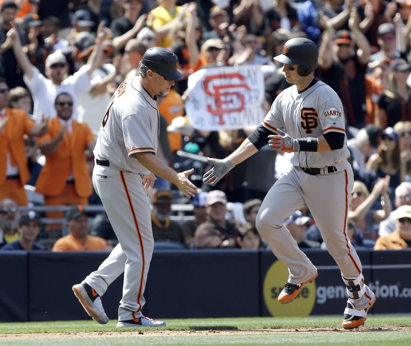 San Francisco Giants' third base coach Phil Nevin, left, congratulates Buster Posey for hitting a solo home run against the San Diego Padres during the third inning of a baseball game in San Diego, Sunday, April 9, 2017. (AP Photo/Alex Gallardo)