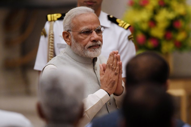 Indian Prime Minister Narendra Modi greets attendees during the swearing-in ceremony of new ministers at the Presidential Palace in New Delhi, India, Sunday, Sept.3, 2017. Modi on Sunday reshuffled some of his key minister's portfolios to refurbish his government's image, which has been dented by falling economic indicators.