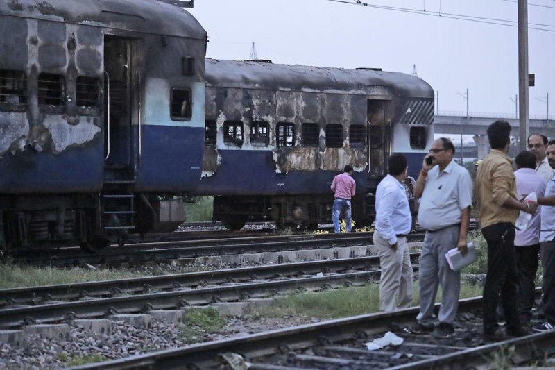 People stand near vandalized train coaches in New Delhi, India, Friday, Aug. 25, 2017. Mobs rampaged across the north Indian town of Panchkula on Friday after a court declared a quasi-religious sect leader guilty of raping two of his followers. Two coaches of an empty train parked in New Delhi's Anand Vihar station were also set on fire.