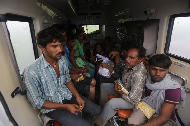 Indian flood victims who were air lifted in an air force helicopter sit inside an ambulance at an airport in Deesa, Gujarat, India, Wednesday, July 26, 2017. At least 29 people have died in the state of Gujarat amid torrential rains. This week's deaths have taken the toll the state to 83 since the start of the monsoon season which runs from June through September.