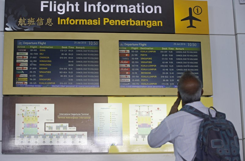 A man checks flight information board at Ngurah Rai International Airport in Bali, Indonesia Friday, June 29, 2018. The Indonesian tourist island of Bali closed its international airport Friday, stranding thousands of travelers, as the Mount Agung volcano gushed a 2,500-meter (8,200-feet) column of ash and smoke.