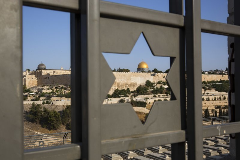 The Islamic Dome of the Rock in Jerusalem's Old City is seen trough a door decorated with a Jewish Star of David, Tuesday, July 25, 2017. Israel has begun dismantling metal detectors it installed a week earlier at the gates of a contested Jerusalem shrine, amid widespread Muslim protests.