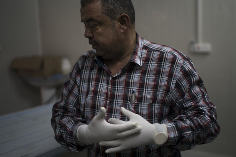 8 2017 photo chief medical assistant raid jassim adjusts his gloves before inspecting a body in a morgue in mosul iraq the morgue staff saw the worst of - Morgue Assistant