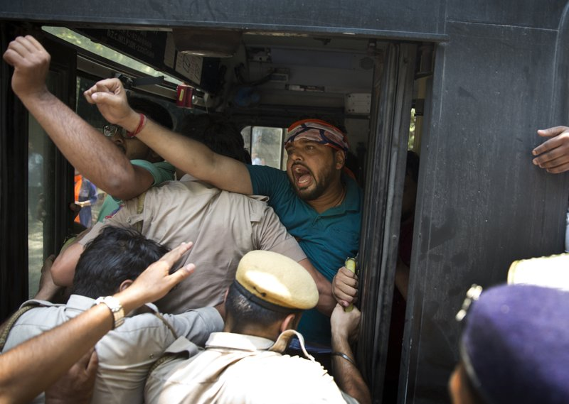 In this May 30, 2017, file photo, Delhi police detain activists of the youth wing of India's ruling party Bharatiya Janata Party during a protest against the slaughter of a calf by Congress party's youth wing members, outside the Congress party headquarters in New Delhi, India. A series of incidents this fall have reinforced fears that anti-Muslim sentiment has hardened in India in the three years since a right-wing Hindu nationalist party led by Prime Minister Narendra Modi swept to power.