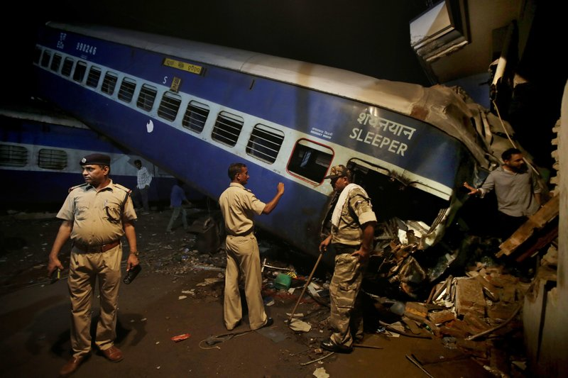 Indian policemen stand guard near the upturned coaches of the Kalinga-Utkal Express after an accident near Khatauli, in the northern Indian state of Uttar Pradesh, India, Sunday, Aug. 20, 2017. Several coaches of a passenger train derailed, causing fatalities and injuries in northern India on Saturday, officials said.