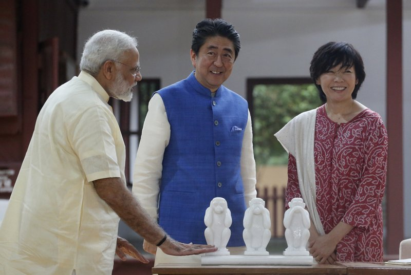 Japanese Prime Minister Shinzo Abe, center, his wife Akie Abe, and Indian Prime Minister Narendra Modi stand beside scultures of three monkeys at Sabarmati Ashram, or Gandhi Ashram, in Ahmadabad, India, Wednesday, Sept. 13, 2017. Abe is on a two-day official visit to India.