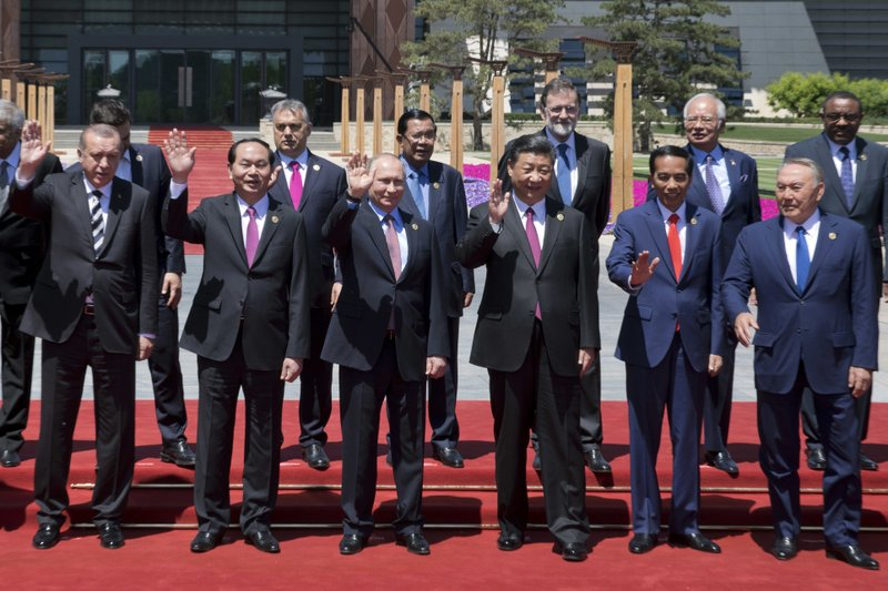 "In this Monday, May 15, 2017, photo, Chinese President Xi Jinping, front row third right, waves with leaders attending the Belt and Road Forum as they pose for a group photo at the Yanqi Lake venue on the outskirt of Beijing. They are, front row from left, Turkish President Recep Tayyip Erdogan, Vietnamese President Tran Dai Quang, Russian President Vladimir Putin, Xi, Indonesian President Joko ""Jokowi"" Widodo and Kazakhstan President Nursultan Nazarbayev, and second row from third left to right, Hungarian Prime Minister Viktor Orban, Cambodian Prime Minister Hun Sen, Spanish Prime Minister Mariano Rajoy, Malaysian Prime Minister Najib Razak and Ethiopian Prime Minister Hailemariam Desalegn."