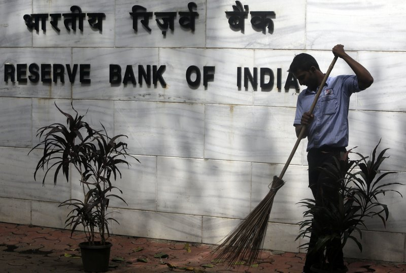 A sweeper cleans the street outside the Reserve Bank of India's headquarters in Mumbai, India, Wednesday, Aug. 2, 2017. India's central bank Wednesday cuts its key interest rate by a quarter of a percentage point on Wednesday, raising hopes of lower borrowing costs for households as inflation ebbs.