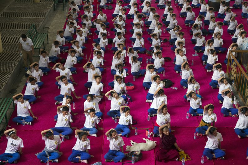 A dog sleeps in the midst of exile Tibetan school children who participate in a joint yoga session at the Tsuglakhang temple to mark the International Yoga Day in Dharmsala, India, Thursday, June 21, 2018. Dozens of school children and government officials participated in the event.