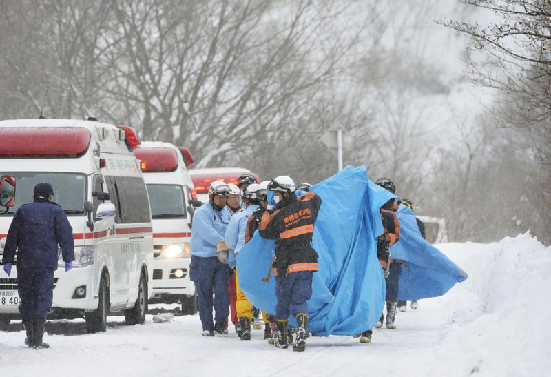Rescuers carry the people who got injured in an avalanche at a ski resort in Nasu, Tochigi prefecture, Monday, March 27, 2017. Eight Japanese high school students are feared dead after being caught in an avalanche Monday during a mountain climbing outing at a ski resort, authorities and media said.
