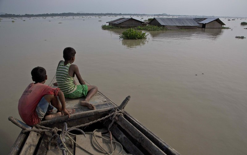 In this Aug. 15, 2017, file photo, flood affected villagers travel by boat in floodwaters in Morigaon district, east of Gauhati, northeastern state of Assam. Heavy monsoon rains have unleashed landslides and floods that killed hundreds of people in recent days and displaced millions more across northern India, southern Nepal and Bangladesh. Deadly landslides and flooding are common across South Asia during the summer monsoon season that stretches from June to September.