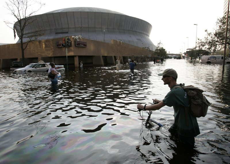 FILE - This Aug, 31, 2005, file photo shows a man pushing his bicycle through flood waters near the Superdome in New Orleans after Hurricane Katrina left much of the city under water. (AP Photo/Eric Gay, File)