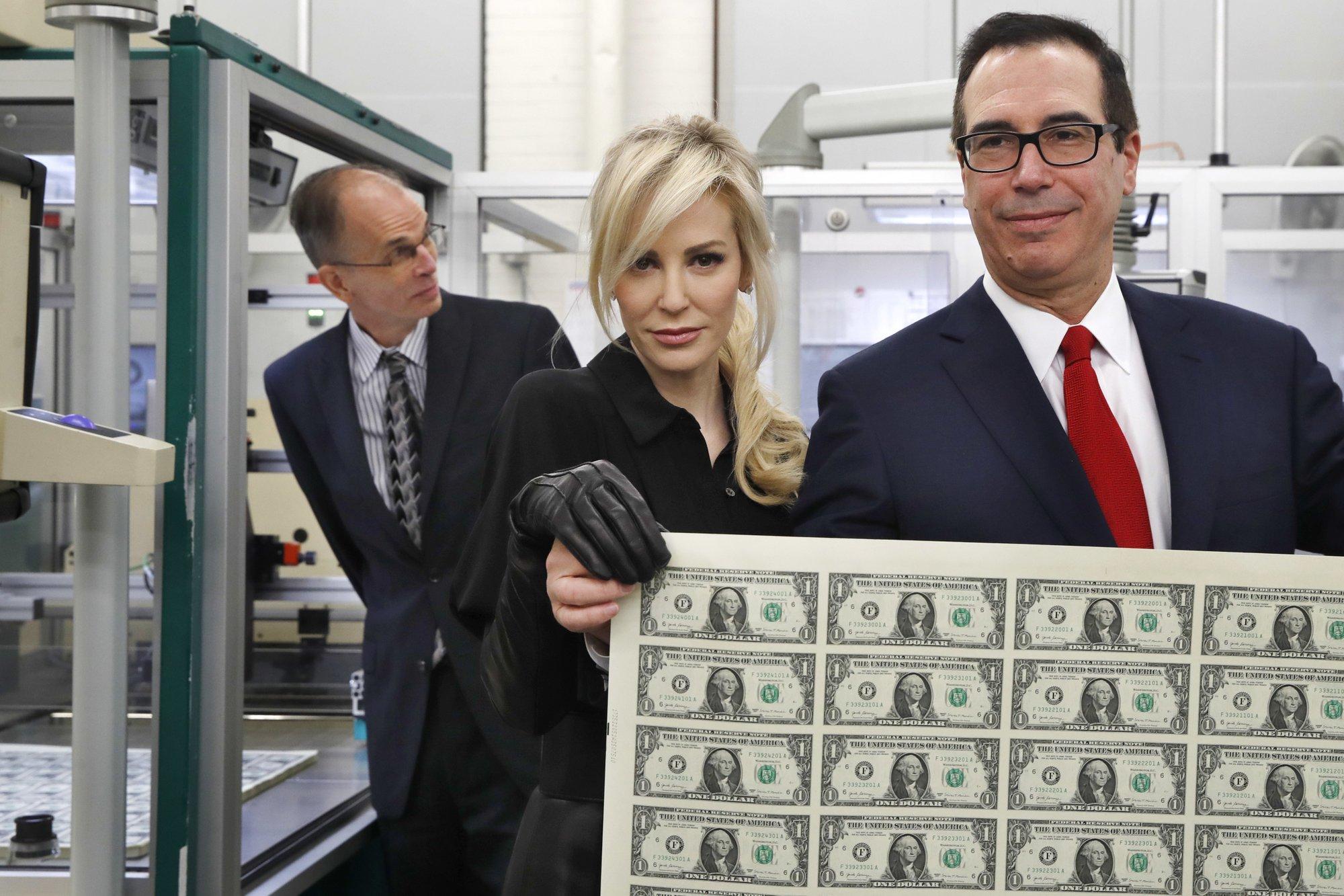 Treasury head, wife mocked for photo of them holding money