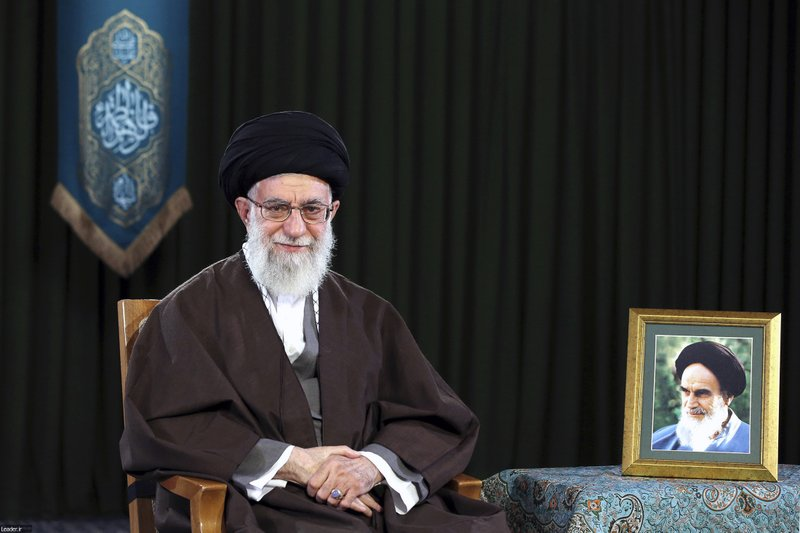 In this picture released by official website of the office of the Iranian supreme leader on Monday, March 20, 2017, Supreme Leader Ayatollah Ali Khamenei sits in a session to deliver his message for the Iranian New Year, Iran. Nowruz, a festival to celebrate the new Persian year starts with the spring. Iranians follow the Persian solar year, and this year, they begin the year 1396. A portrait of the late revolutionary founder Ayatollah Khomeini is placed at right.
