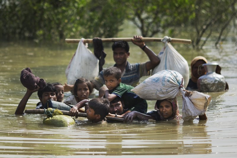 In this Tuesday, Sept. 5, 2017, file photo, a Rohingya family reaches the Bangladesh border after crossing a creek of the Naf river on the border with Myanmmar, in Cox's Bazar's Teknaf area.