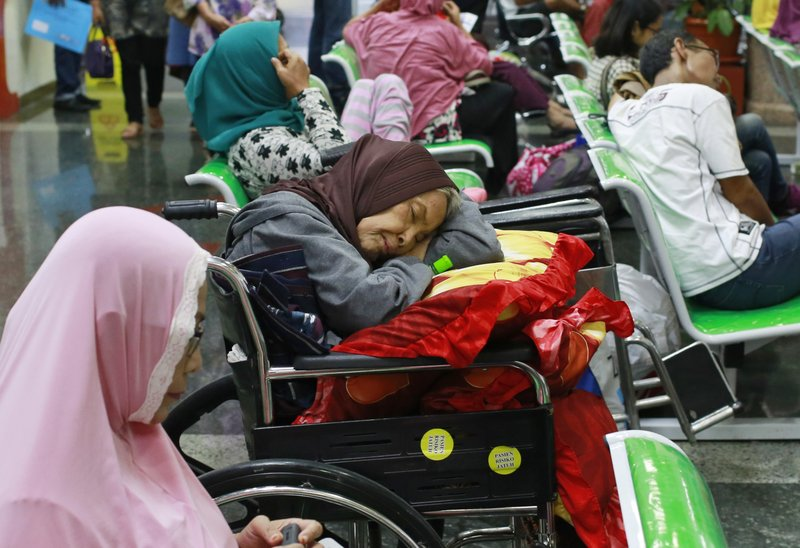 "A patient takes a nap on her wheelchair as she waits with others at the registration desk at Dharmais Cancer Hospital in Jakarta, Indonesia, Monday, May 15, 2017 as the hospital's information system is in trouble by cyberattack. Global cyber chaos was spreading Monday as companies booted up computers at work following the weekend's worldwide ""ransomware"" cyberattack. The extortion scheme created chaos in 150 countries and could wreak even greater havoc as more malicious variations appear."