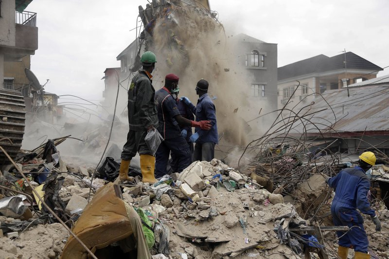 Rescue workers looking for survivors watch as debris falls from a collapsed building in a densely populated neighborhood in Lagos, Nigeria, Wednesday, July 26, 2017. Officials said a four-story residential building collapsed in Nigeria's largest city resulting in multiple casualties. Building collapses are not uncommon in the West African powerhouse where corruption is rampant and infrastructure often poor.