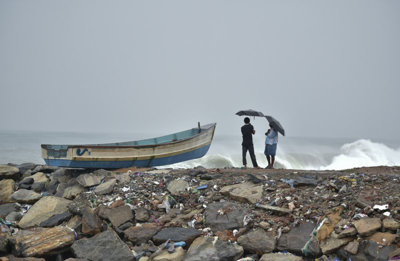 Two men hold umbrellas to protect themselves from the rain as they stand next to a fishing boat on the Arabian Sea coast in Thiruvananthapuram, Kerala state, India, Friday, Dec.1, 2017. Dozens of fishermen were rescued Friday from the sea which is very rough under the influence of Cyclone Ockhi.