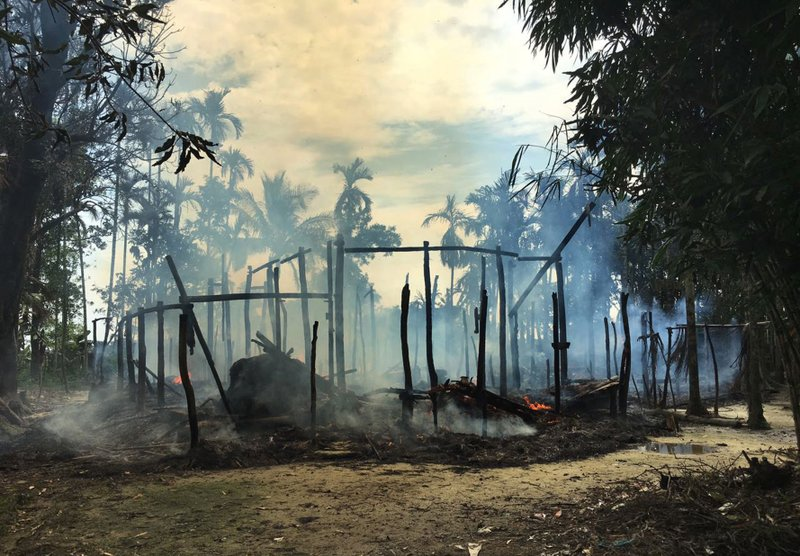 In this Thursday, Sept. 7, 2017, file photo, smoke rises from a burned house in Gawdu Zara village, northern Rakhine state, Myanmar. Journalists saw new fires burning Thursday in the Myanmar village that had been abandoned by Rohingya Muslims, and where pages from Islamic texts were seen ripped and left on the ground.