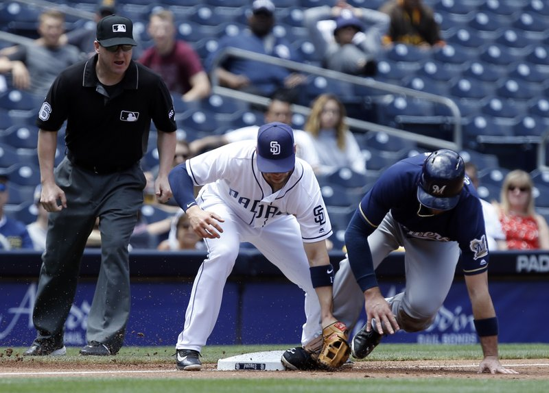 Milwaukee Brewers' Travis Shaw, right, beats the throw to San Diego Padres third baseman Ryan Schimpf on a wild pitch as umpire Ryan Blakney, left, watches to make the call during the second inning of a baseball game in San Diego, Thursday, May 18, 2017. (AP Photo/Alex Gallardo)