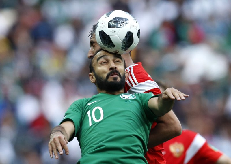 Saudi Arabia's Mohammed Alsahlawi, foreground, jumps for the ball with Russia's Alexander Samedov during the group A match between Russia and Saudi Arabia which opens the 2018 soccer World Cup at the Luzhniki stadium in Moscow, Russia, Thursday, June 14, 2018.
