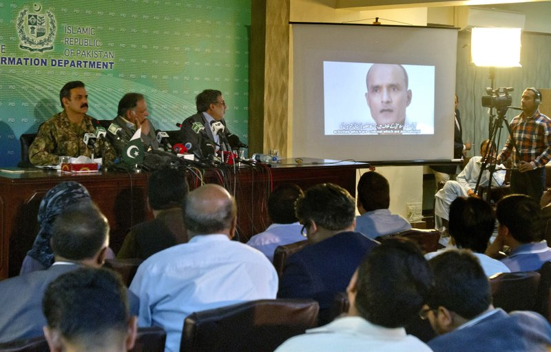 In this March 29, 2016 photo, journalists look a image of Indian naval officer Kulbhushan Jadhav, who was arrested in March 2016, during a press conference by Pakistan's army spokesman and the Information Minister, in Islamabad, Pakistan. The army said in a statement Monday, April 10, 2017, that Jadhav was sentenced to death on charges of espionage and sabotage. Pakistan says Jadhav was an Indian intelligence official who aided and financed terrorist activities.