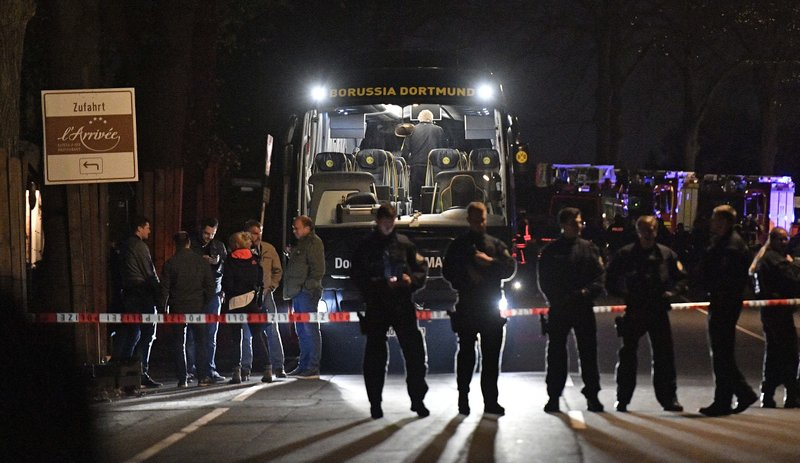 Police officers stand in front of Dortmund's damaged team bus after an explosion before the Champions League quarterfinal soccer match between Borussia Dortmund and AS Monaco in Dortmund, western Germany, Tuesday, April 11, 2017.