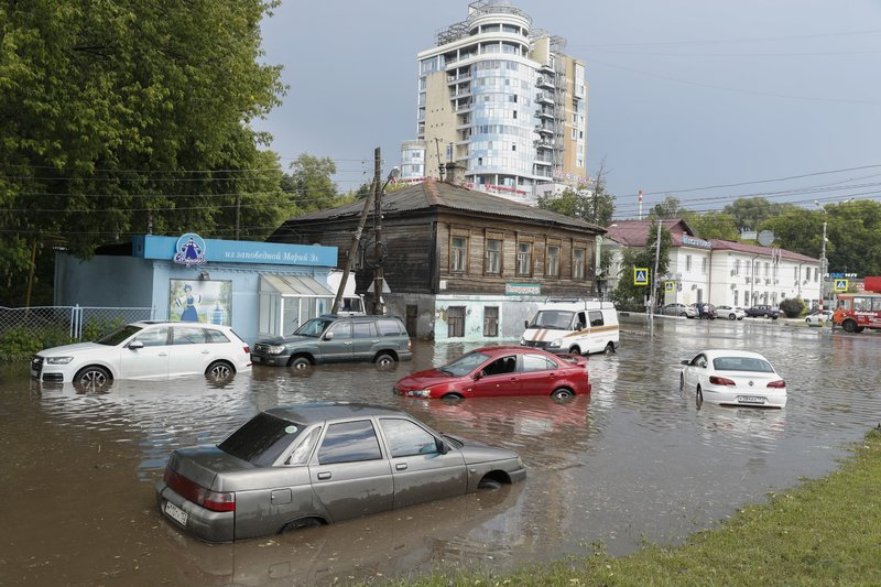 Cars sit in flood water after a heavy rain in Nizhny Novgorod, Russia, Tuesday, June 19, 2018. Nizhny Novgorod Stadium is hosting six matches during the Russia 2018 World Cup.