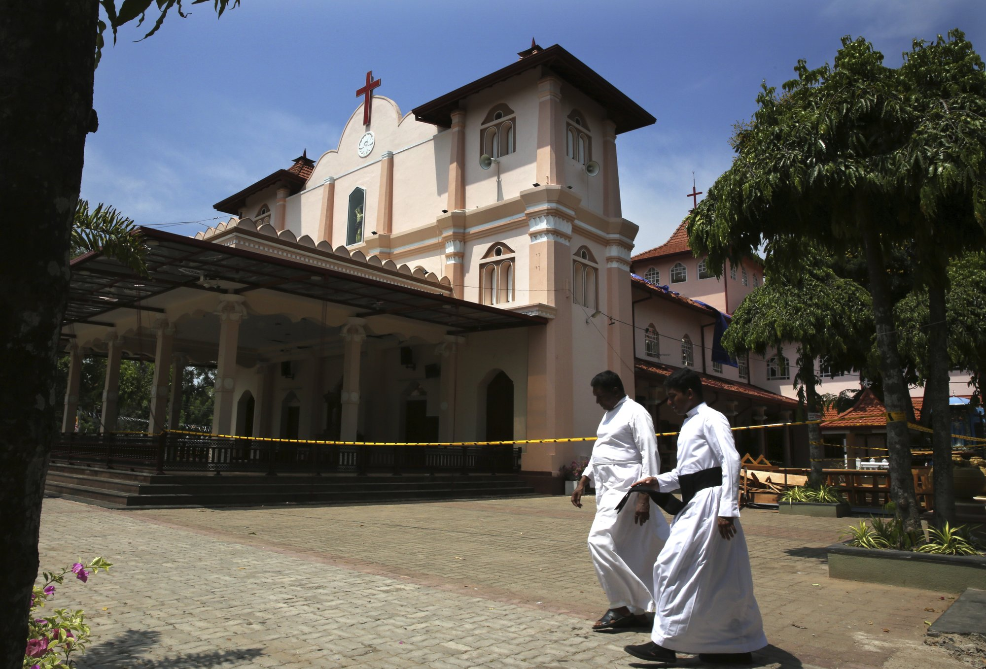 In this Thursday, April 25, 2019 photo, Catholic priests walk outside St. Sebastian's Church, where a suicide bomber blew himself up on Easter Sunday in Negombo, north of Colombo, Sri Lanka. Nearly a week later, the smell of death is everywhere, though the bodies are long gone. From inside, you see destruction wherever you look. But from outside the church, if you ignore the police tape and if you're standing far enough away, you might think nothing had happened there at all. (AP Photo/Manish Swarup)