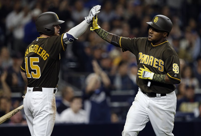 San Diego Padres' Cory Spangenberg, left, congratulates Erick Aybar for scoring on a sacrifice fly hit by Manuel Margot against the Los Angeles Dodgers during the fifth inning of a baseball game in San Diego, Friday, May 5, 2017. (AP Photo/Alex Gallardo)