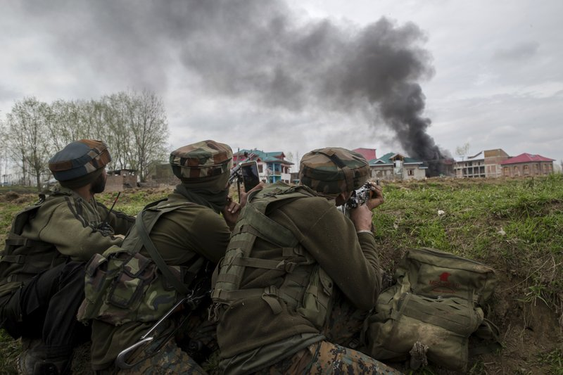 An Indian army soldier takes a video with his mobile phone as smoke rises from a house during a gun battle in Chadoora town, about 25 kilometers (15 miles) south of Srinagar, Indian controlled Kashmir, Tuesday, March 28, 2017. The gunbattle began after police and soldiers cordoned off the southern town of Chadoora following a tip that at least one militant was hiding in a house, said Inspector-General Syed Javaid Mujtaba Gillani.