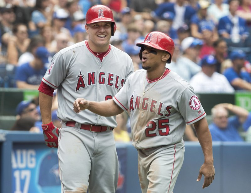 Los Angeles Angels Ben Revere all smiles with team mate Mike Trout after scoring the winning run in the ninth inning.