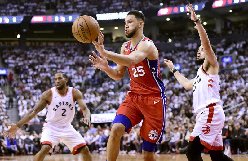 096fa1bad Philadelphia 76ers guard Ben Simmons (25) passes the ball as Toronto  Raptors forward Kawhi Leonard (2) and teammate Fred VanVleet (23) look on  during first ...