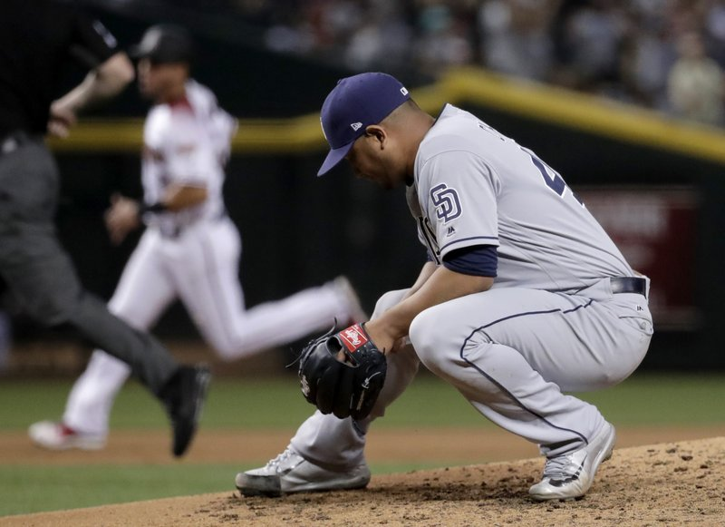 San Diego Padres pitcher Jhoulys Chacin kneels as Arizona Diamondbacks' Chris Owings rounds the bases after hitting a grand slam home run during the fifth inning of a baseball game, Monday, April 24, 2017, in Phoenix. (AP Photo/Matt York)