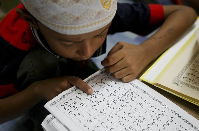 In this Tuesday, Sept. 12, 2017, photo, a Rohingya Muslim child living in Malaysia recites from the holy Quran at a school in Klang, on the outskirts of Kuala Lumpur, Malaysia. Recent violence in Myanmar has driven hundreds of thousands of Rohingya Muslims to seek refuge across the border in Bangladesh. There are some 56,000 Rohingya refugees registered with the U.N. refugee agency in Malaysia, with an estimated 40,000 more whose status has yet to be assessed.