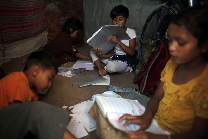 In this Sunday, Sept. 10, 2017, photo, Rohingya children study inside a temporary shelter at a camp in Kathmandu, Nepal. Recent violence in Myanmar has driven hundreds of thousands of Rohingya Muslims to seek refuge across the border in Bangladesh. Only about 250 Rohingya live in Nepal since anti-Muslim riots erupted in Myanmar in 2012, according to the U.N. refugee agency, which offers them education and medical support. The refugees live in a ramshackle camp carved out on a slope on the outskirts of the capital, Kathmandu. Their huts of tin, bamboo and plastic sheets are connected by narrow stone steps.