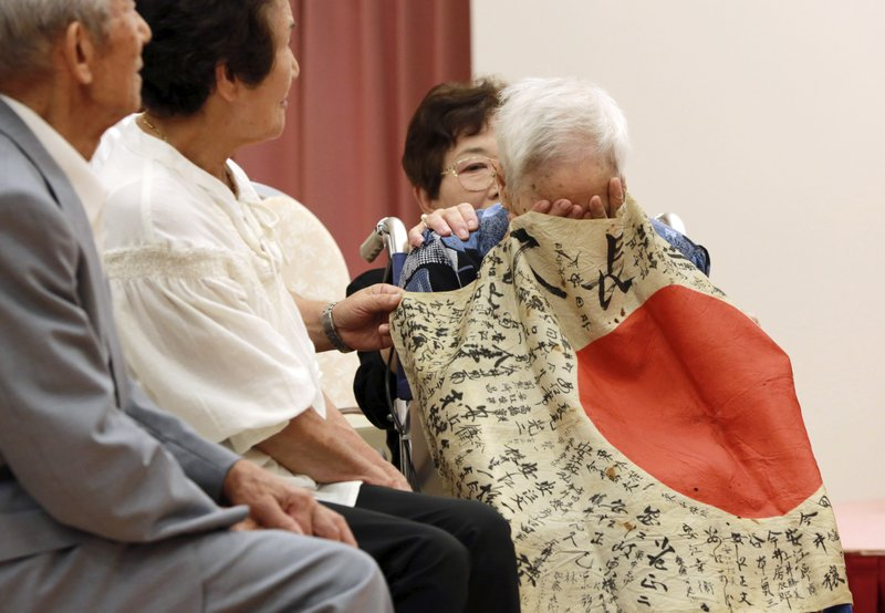 In this Tuesday, Aug. 15, 2017, file photo, Sayoko Furuta, right, 93, reacts as she is covered with a Japanese flag with hand written messages which was owned by her brother Sadao Yasue, who was killed in the Pacific during World War II, during a ceremony in Higashishirakawa, in central Japan's Gifu prefecture. Former U.S. Marine Marvin Strombo handed the calligraphy-covered flag he took from the fallen Japanese soldier 73 years ago back to Sadao Yasue's younger brother and sisters Tuesday.