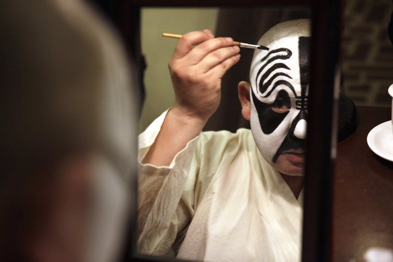 "In this Saturday, May 13, 2017, photo, Zhao Hailong puts on makeup for his lead role in the Peking Opera classic ""Farewell My Concubine"" at a theater in Beijing. When Zhao was a teenager he played a small role in the award-winning film ""Farewell My Concubine,"" the story of the life-long friendship between two men who met as apprentices in China's famed Peking opera. Today, he is the lead on stage in the Peking Opera classic of the same name."