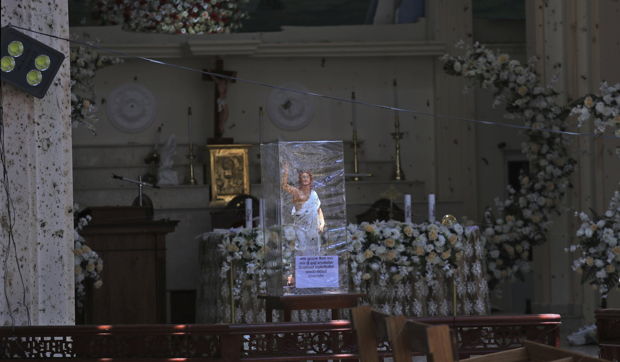 In this Thursday, April 25, 2019 photo, a statue of Jesus Christ stands on the altar of St. Sebastian's Church in Negombo, north of Colombo, Sri Lanka. Nearly a week later, the smell of death is everywhere, though the bodies are long gone. Yet somehow, there's a beauty to St. Sebastian's, a neighborhood church in a Catholic enclave north of Sri Lanka's capital, where a man calmly walked in during Easter services with a heavy backpack and blew himself up. There is beauty in the little statues that refused to fall over, and despite the swarms of police and soldiers who seem to be everywhere now in the streets of the seaside town of Negombo. (AP Photo/Manish Swarup)