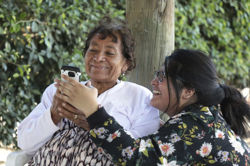 In this Dec. 23, 2016 photo, Tamara Alcala Dominguez shares cell phone photos with her grandmother Petra Bello Suarez in their home town of Molcaxac, Puebla, Mexico. During her first return since she left Mexico for the U.S. as a toddler, Alcala followed her grandmother everywhere, to the store, to meet neighbors and to the town holiday party. (AP Photo/Pablo Spencer)