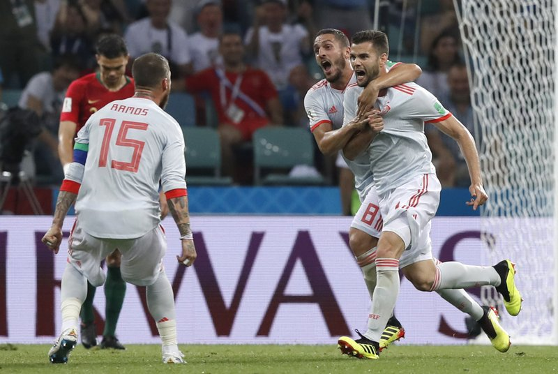 Spain's Nacho, right, celebrates with teammate Spain's Koke, and Spain's Sergio Ramos, left, after scoring his sides 3rd goal during the group B match between Portugal and Spain at the 2018 soccer World Cup in the Fisht Stadium in Sochi, Russia, Friday, June 15, 2018.