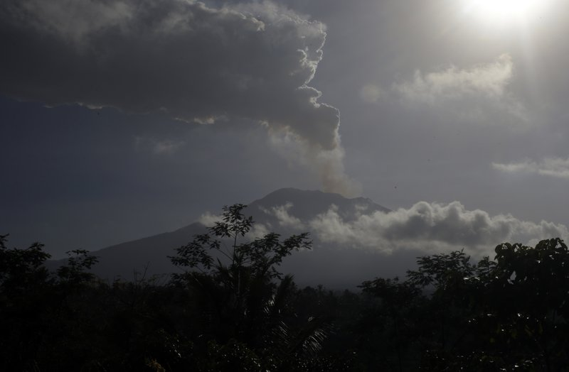 Mount Agung volcano spews smoke, seen in Karangasem, Bali, Indonesia Friday, June 29, 2018. The Indonesian tourist island of Bali closed its international airport Friday, stranding thousands of travelers, as the Mount Agung volcano gushed a 2,500-meter (8,200-feet) column of ash and smoke.