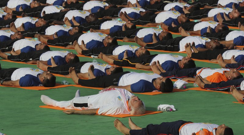 Indian Prime Minister Narendra Modi, center, performs yoga along with thousands of Indians to mark International Day of Yoga in Dehradun, India, Thursday, June 21, 2018. Yoga enthusiasts across the world Thursday took part in mass yoga events to mark International Yoga Day.